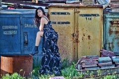 Mujer en un vestido largo con el pelo marrón de largo que fluye y la pierna doblada contra el contexto de almacenes abandonados Imagen de archivo