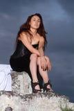Mujer en un vestido negro en un fondo del cielo nublado imagenes de archivo