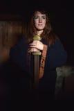 Mujer en un vestido oscuro con la espada Fotografía de archivo libre de regalías
