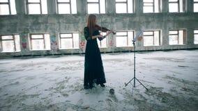 Mujer en un vestido en tocar el violín en un pasillo desalinado almacen de metraje de vídeo