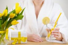 mujer en una albornoz blanca En los tulipanes del amarillo de la tabla, regalo y Fotografía de archivo