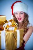 Mujer en una alineada y un sombrero rojos de Santa con un regalo grande Fotografía de archivo