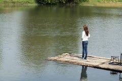 Mujer en una balsa de bambú en el río foto de archivo