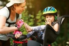 mujer en una bicicleta con la pequeña hija imagenes de archivo