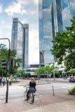 Mujer en una bicicleta con los edificios de oficinas altos en el fondo Fotografía de archivo