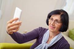 Mujer en una butaca con un teléfono Imágenes de archivo libres de regalías