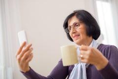 Mujer en una butaca con un teléfono Imagen de archivo