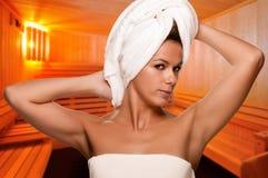 Mujer en una cabina de la sauna Fotos de archivo libres de regalías