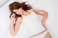 Mujer en una cama Imagen de archivo libre de regalías