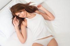 Mujer en una cama Imágenes de archivo libres de regalías