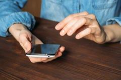 Mujer en una camisa del dril de algodón que sostiene el teléfono móvil y que se sienta en un de madera Foto de archivo