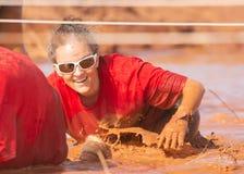 Mujer en una camisa roja y gafas de sol blancas que sonríe mientras que salpica con un obstáculo del fango durante un funcionamie imagen de archivo libre de regalías