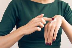 Mujer en una camiseta verde y una manicura marrón que aplican el cre de la mano Fotos de archivo