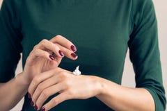 Mujer en una camiseta verde y una manicura marrón que aplican el cre de la mano Foto de archivo libre de regalías