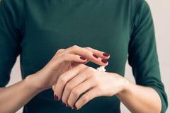 Mujer en una camiseta verde y una manicura marrón que aplican la crema de la mano Fotografía de archivo libre de regalías