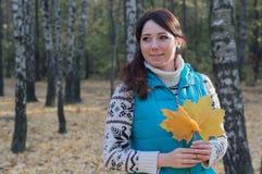 Mujer en una chaqueta azul con las hojas amarillas Imagenes de archivo