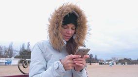 Mujer en una chaqueta blanca del plumón que se sienta en un banco en la playa y que mecanografía un mensaje en el teléfono móvil metrajes