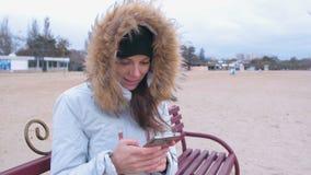 Mujer en una chaqueta blanca del plumón que se sienta en un banco en la playa y que mecanografía un poste en medios sociales en e almacen de metraje de vídeo