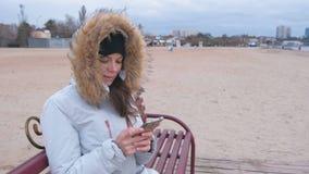 Mujer en una chaqueta blanca del plumón que se sienta en un banco en la playa y que mira el teléfono móvil almacen de metraje de vídeo