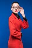 Mujer en una chaqueta roja con el lápiz labial Imagen de archivo libre de regalías