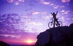 Mujer en una cima de la montaña con la bici Imagen de archivo libre de regalías