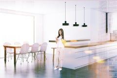 Mujer en una cocina blanca de lujo entonada Fotografía de archivo