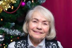 Mujer en una edad madura contra el árbol de navidad Imagenes de archivo