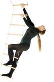 Mujer en una escala de cuerda Fotos de archivo