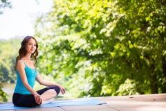 Mujer en una estera de la yoga a relajarse Fotos de archivo libres de regalías