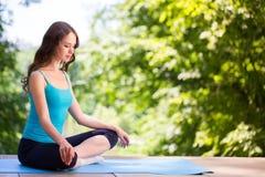 Mujer en una estera de la yoga a relajarse Foto de archivo libre de regalías