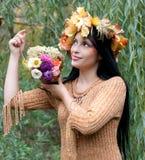 Mujer en una guirnalda de las hojas de otoño Imagenes de archivo