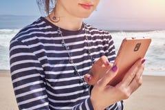 Mujer en una lectura rayada de la camiseta en el smartphone en la playa, día de verano imagen de archivo