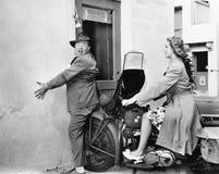 Mujer en una moto que corre en una pared y que golpea a un hombre (todas las personas representadas no son vivas más largo y ning Foto de archivo