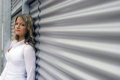 Mujer en una pared del metal Imágenes de archivo libres de regalías