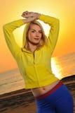 Mujer en una playa en la puesta del sol Imagen de archivo libre de regalías