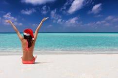 Mujer en una playa tropical que disfruta de su partida de la Navidad fotos de archivo libres de regalías