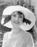 Mujer en una sonrisa brimmed amplia del sombrero (todas las personas representadas no son vivas más largo y ningún estado existe  imágenes de archivo libres de regalías