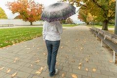 Mujer en vaqueros que camina con un paraguas en la lluvia en un otoño fotografía de archivo libre de regalías