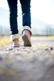 Mujer en vaqueros y botas que caminan a lo largo de una trayectoria rural Foto de archivo