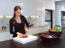 Mujer en verdura del corte de la cocina Imagen de archivo libre de regalías