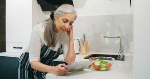 Mujer en verduras de la cocina, tableta metrajes