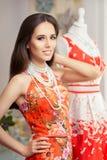 Mujer en vestido de flores rojo en tienda de la moda Imagenes de archivo