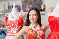 Mujer en vestido de flores rojo en tienda de la moda Foto de archivo libre de regalías