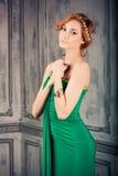 Mujer en vestido de noche verde en el estudio de la moda Fotos de archivo