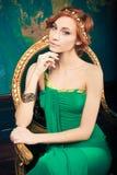 Mujer en vestido de noche verde en silla del vintage Imagenes de archivo