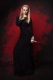 Mujer en vestido negro con un cuchillo imagenes de archivo