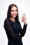 Mujer en vestido negro de moda usando smartphone Fotografía de archivo