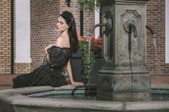Mujer en vestido negro en fontain Imagen de archivo libre de regalías