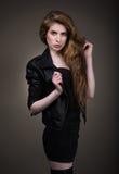 Mujer en vestido negro, la chaqueta de cuero y medias Foto de archivo libre de regalías