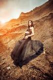 Mujer en vestido negro largo en el barranco de la arena imagenes de archivo